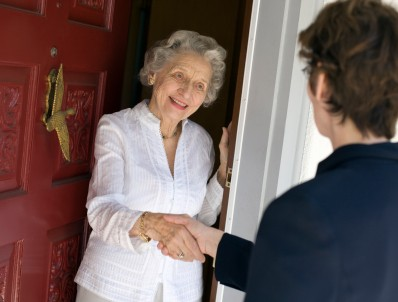 Elderly lady shaking hands at the door